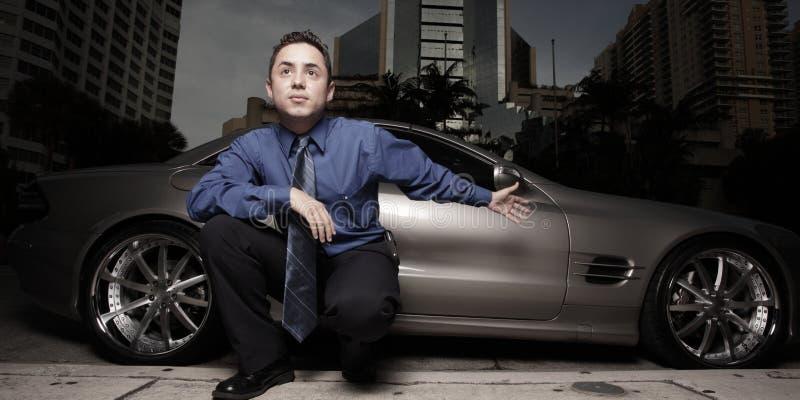 Mens op de straat met zijn luxesportwagen stock fotografie