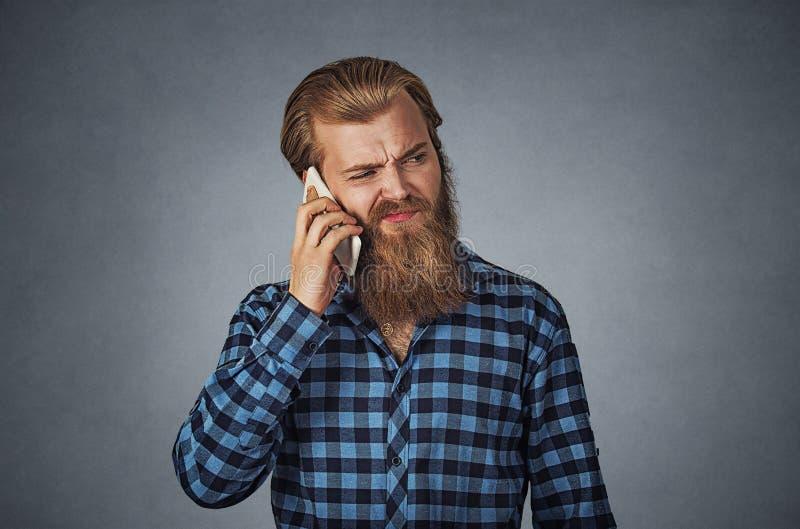 Mens op de telefoon met concept van de hoofdpijn het Cellulaire mobiele straling royalty-vrije stock foto's