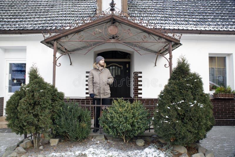 Mens op een portiek van wit dorpshuis met groene vooruit struiken royalty-vrije stock afbeeldingen