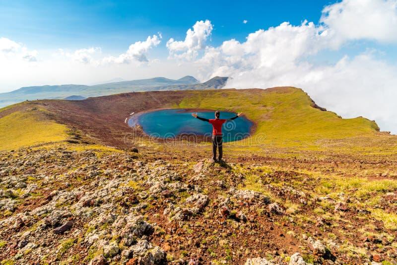 Mens op een top van Azhdahak-vulkaan het letten op kratermeer, Geghama-bergen, Armenië royalty-vrije stock foto