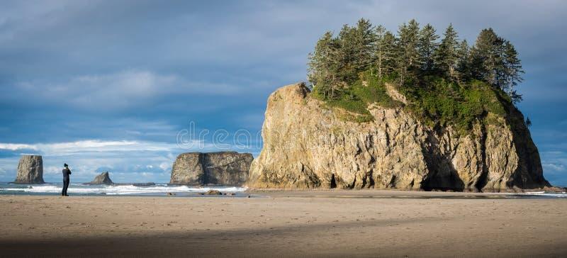 Mens op een Vreedzame kuststrand met overzeese stapels op de achtergrond royalty-vrije stock afbeeldingen