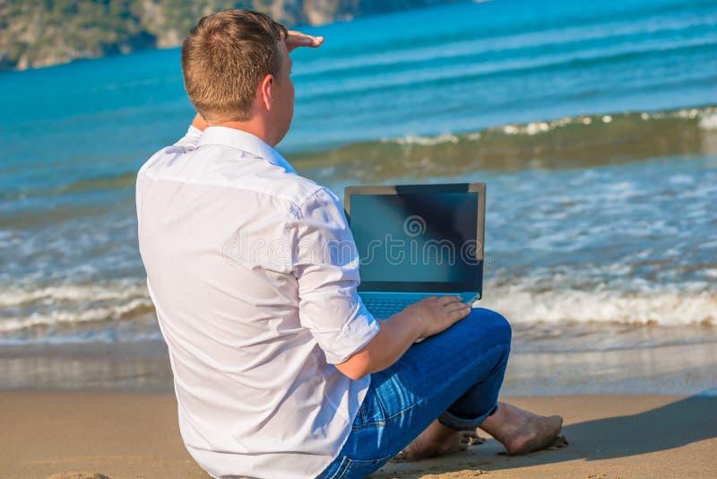 Mens op een woestijneiland met laptop stock fotografie