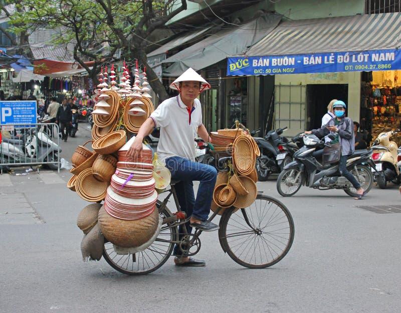 Mens op fiets die de hoeden van Hanoi verkopen stock foto