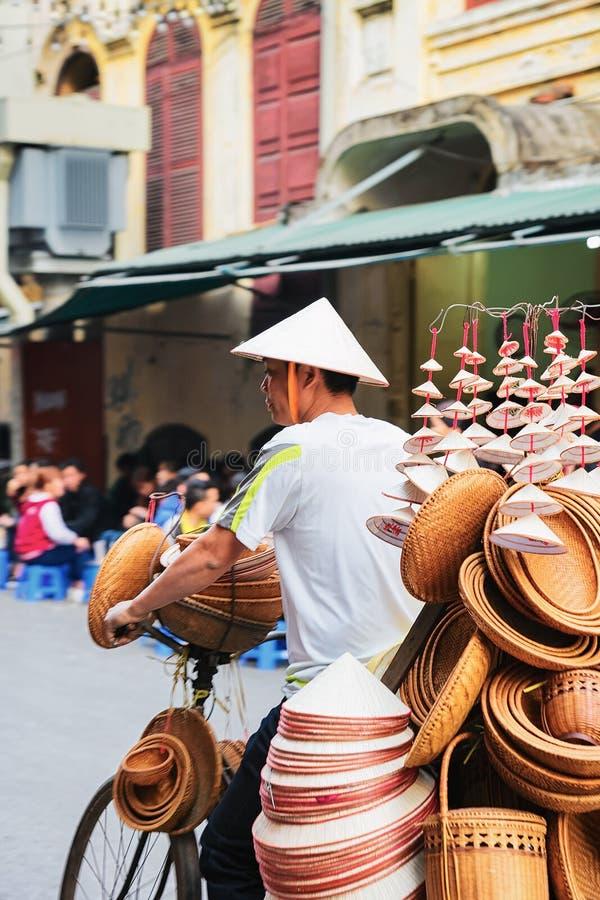 Mens op fiets die traditionele Vietnamese hoeden in Hanoi verkopen stock afbeelding