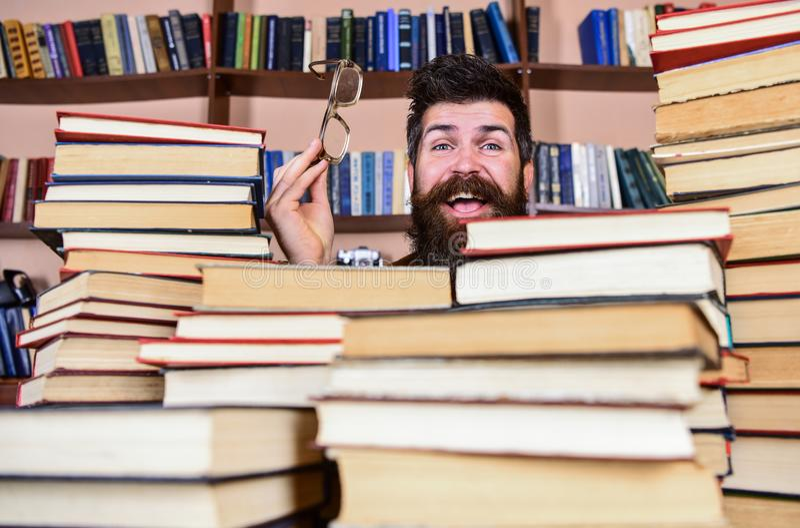 Mens op gelukkig gezicht tussen stapels van boeken in bibliotheek, boekenrekken op achtergrond De leraar of de student met baard  royalty-vrije stock foto