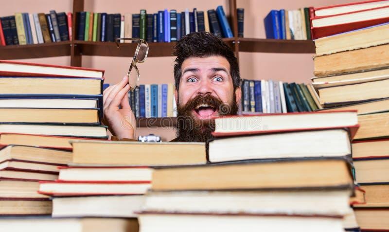 Mens op gelukkig gezicht tussen stapels van boeken in bibliotheek, boekenrekken op achtergrond wetenschappelijk onderzoekconcept  stock foto's