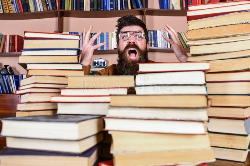 Mens op geschokt gezicht tussen stapels van boeken in bibliotheek, boekenrekken op achtergrond De leraar of de student met baard  royalty-vrije stock afbeeldingen