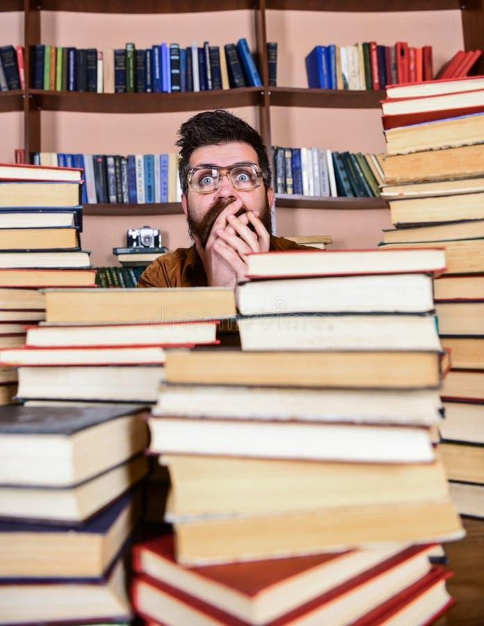 Mens op geschokt gezicht tussen stapels van boeken in bibliotheek, boekenrekken op achtergrond Wetenschappelijk ontdekkingsconcep royalty-vrije stock afbeeldingen