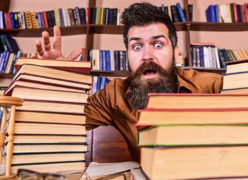 Mens op geschokt gezicht tussen stapels van boeken, terwijl het bestuderen in bibliotheek, boekenrekken op achtergrond Leraar of  royalty-vrije stock fotografie