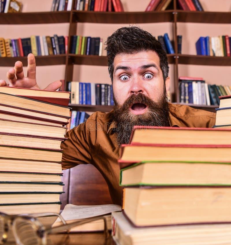 Mens op geschokt gezicht tussen stapels van boeken, terwijl het bestuderen in bibliotheek, boekenrekken op achtergrond Uiterste t royalty-vrije stock fotografie