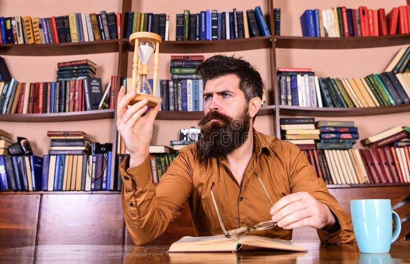 Mens op het bezige boek van de gezichtslezing, boekenrekken op achtergrond Les en tijdconcept De wetenschapper met oogglazen zit  stock foto
