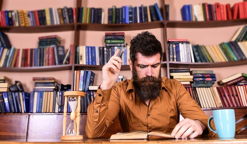 Mens op het bezige boek van de gezichtslezing, boekenrekken op achtergrond Onderwijs en wetenschapsconcept Leraar of student met  royalty-vrije stock foto's