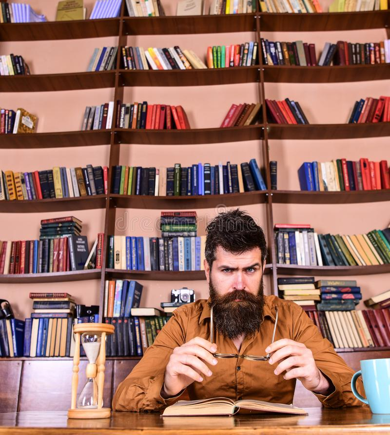 Mens op het bezige boek van de gezichtslezing, boekenrekken op achtergrond Onderwijs en wetenschapsconcept De wetenschapper zit b stock afbeelding