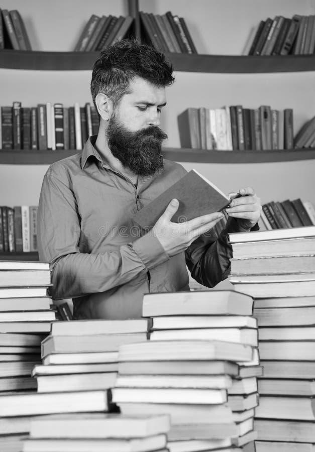 Mens op het bezige nadenkende boek van de gezichtslezing, boekenrekken op achtergrond Leraar of student die met baard in biblioth royalty-vrije stock fotografie