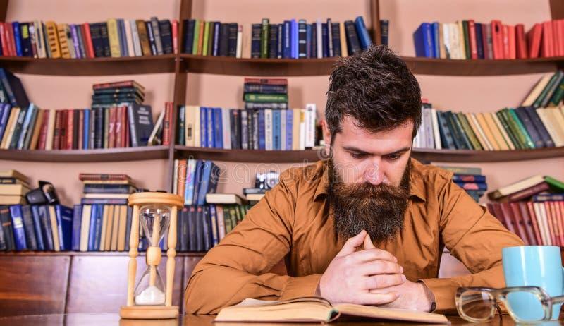 Mens op het geconcentreerde boek van de gezichtslezing, het bestuderen, boekenrekken op achtergrond Leraar of student die met baa royalty-vrije stock afbeelding
