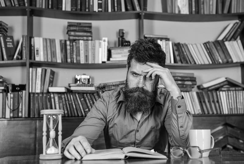 Mens op het geconcentreerde boek van de gezichtslezing, het bestuderen, boekenrekken op achtergrond Zelfonderwijsconcept De mens  royalty-vrije stock afbeeldingen