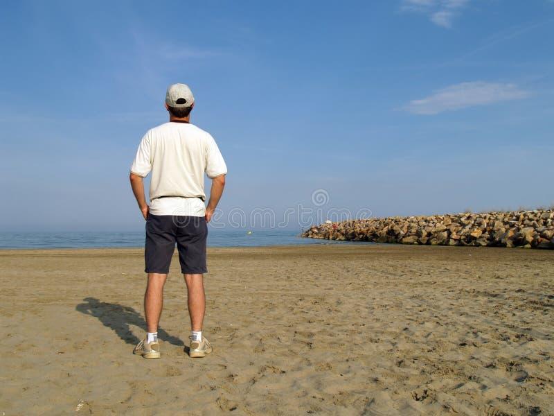 Mens op het strand stock afbeeldingen
