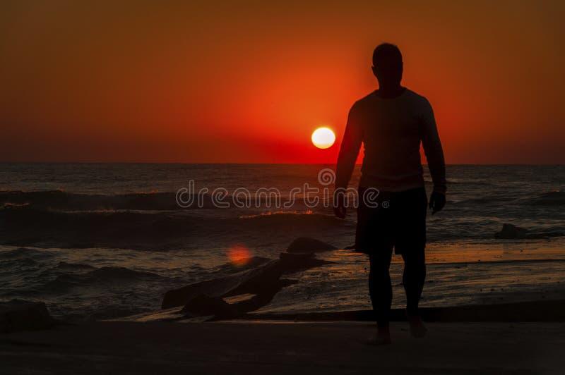 Mens op het strand tijdens zonsopgang stock fotografie
