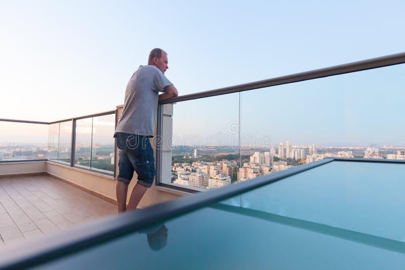 Mens op hoog eindbalkon binnen de stad in royalty-vrije stock fotografie