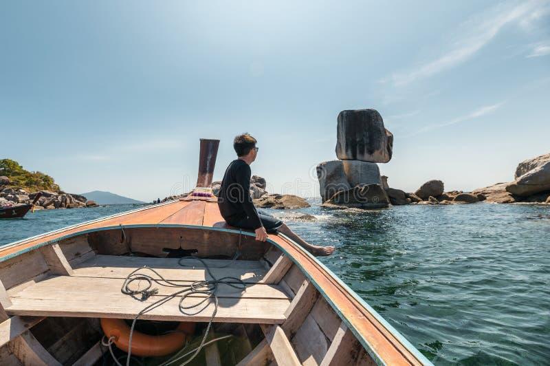 Mens op houten boot die bij natuurlijke rotsen reizen gestapeld in tropische overzees stock afbeelding