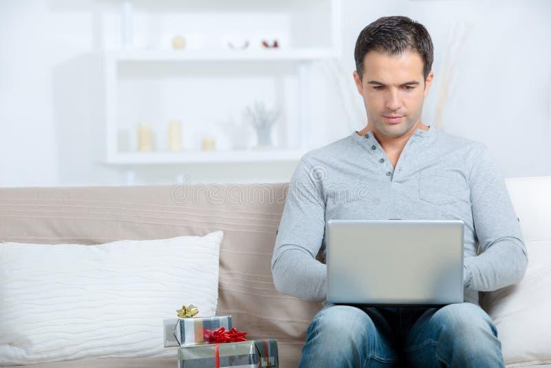 Mens op Internet-giften naast hem stock afbeeldingen