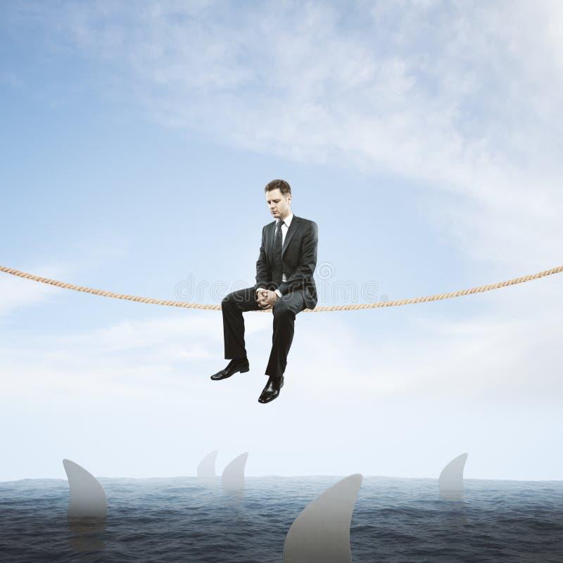 Mens op kabel boven haaien stock afbeeldingen