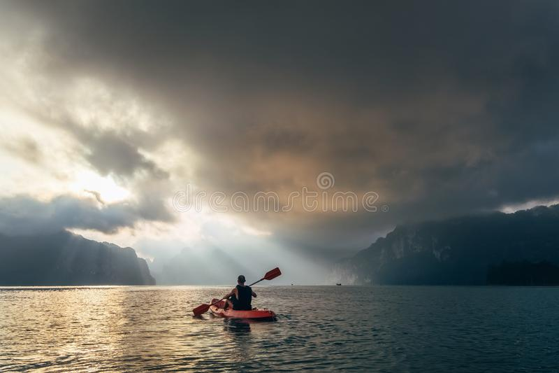 Mens op kajak meetting zonsopgang op Cheow Lan Lake, het nationale Park van Khao Sok, Thailand royalty-vrije stock foto