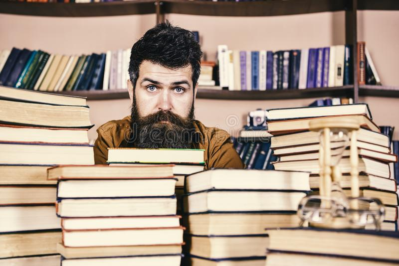 Mens op kalm gezicht tussen stapels van boeken, terwijl het bestuderen in bibliotheek, boekenrekken op achtergrond bibliofielconc royalty-vrije stock afbeeldingen