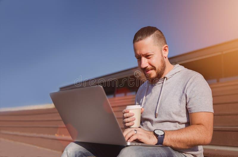 Mens op laptop van het koffiepauzegebruik royalty-vrije stock foto's
