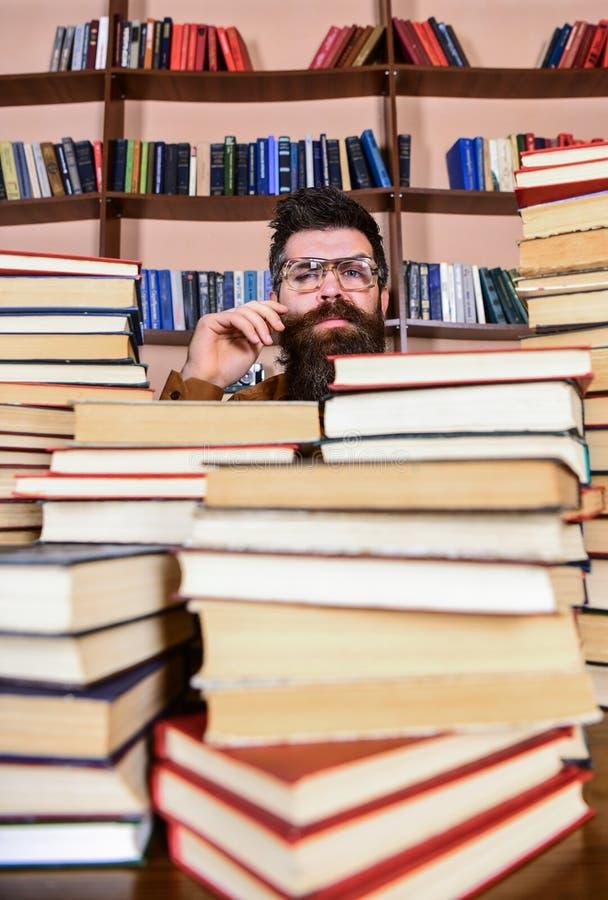 Mens op nadenkend gezicht tussen stapels van boeken in bibliotheek, boekenrekken op achtergrond De leraar of de student met baard royalty-vrije stock afbeeldingen
