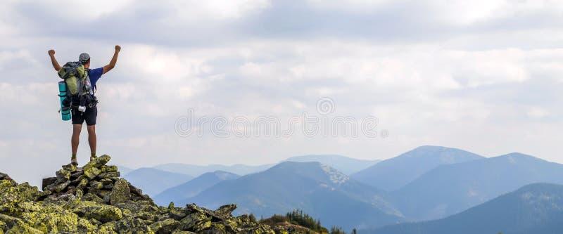 Mens op piek van berg Emotionele scène Jonge mens met backpac royalty-vrije stock afbeeldingen