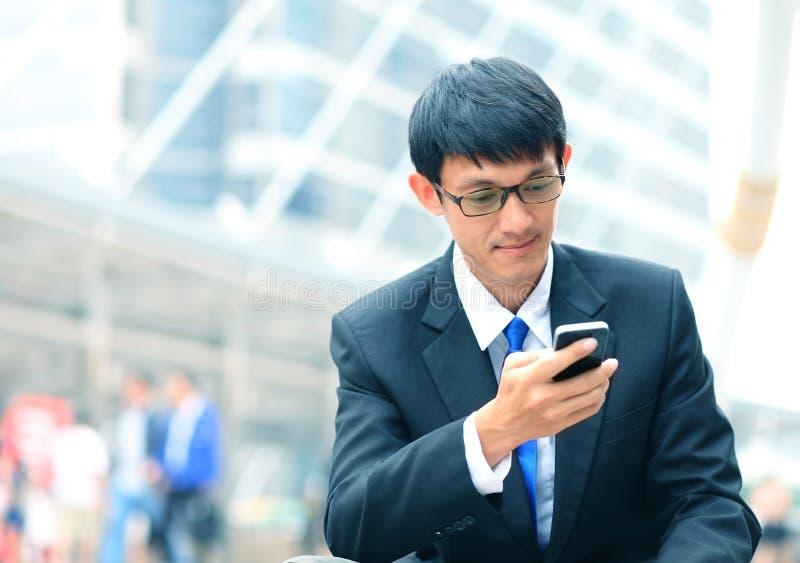 Mens op slimme telefoon - jonge bedrijfsmens Toevallig stedelijk beroep stock foto