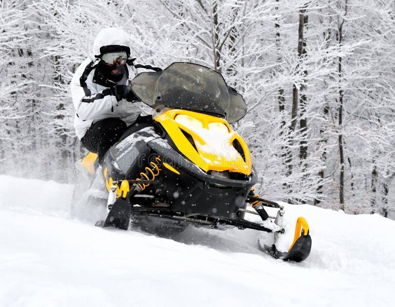Mens op sneeuwscooter stock foto's