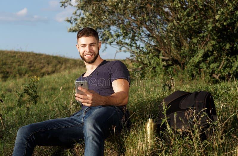 Mens op stijging in aard die telefoon met behulp van stock foto