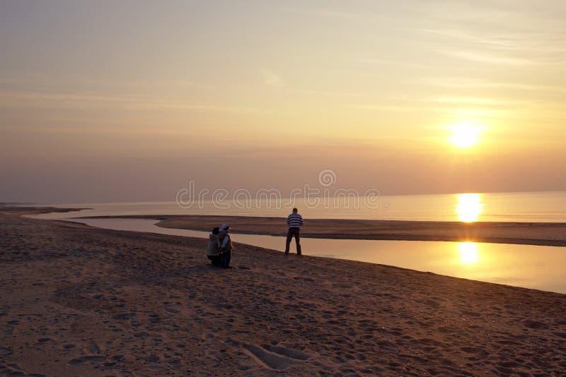 Mens op strand bij zonsondergang stock foto's