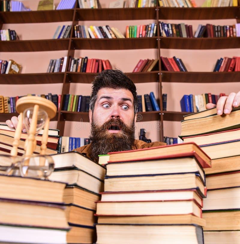 Mens op verrast gezicht tussen stapels van boeken, terwijl het bestuderen in bibliotheek, boekenrekken op achtergrond Leraar of s stock fotografie