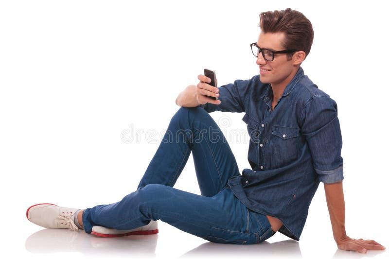 Mens op vloer het texting royalty-vrije stock afbeelding