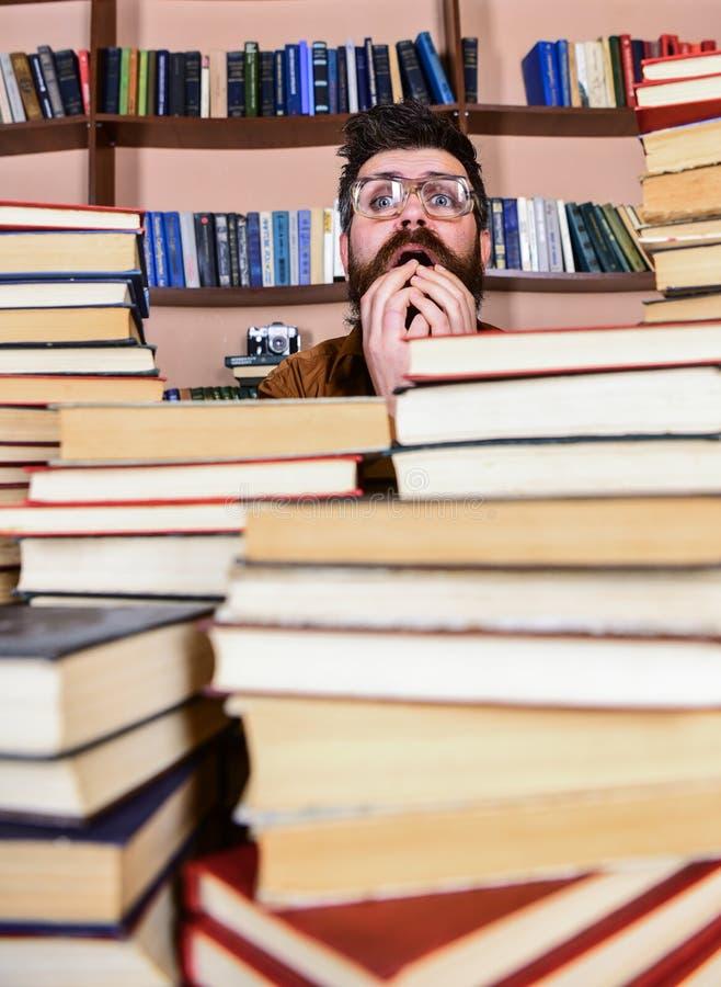 Mens op zenuwachtig gezicht tussen stapels van boeken in bibliotheek, boekenrekken op achtergrond De leraar of de student met baa stock foto