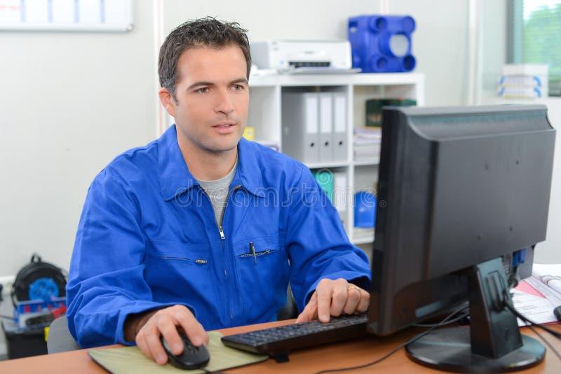 Mens in overall op computer stock foto