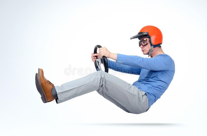 Mens in rode helm en van de beschermende brillenauto bestuurder met stuurwiel, autoconcept stock foto