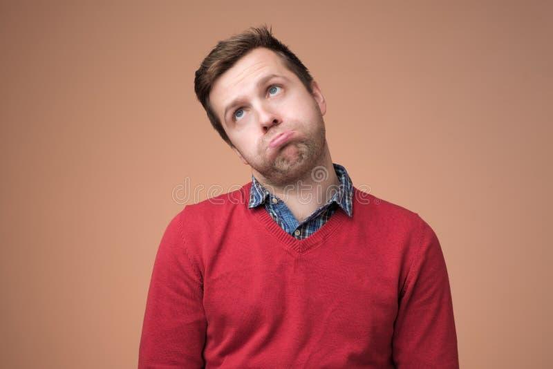 Mens in rode sweater die zijn wangen, voelen puffen omhoog gevoed als vermoeide heis royalty-vrije stock afbeeldingen