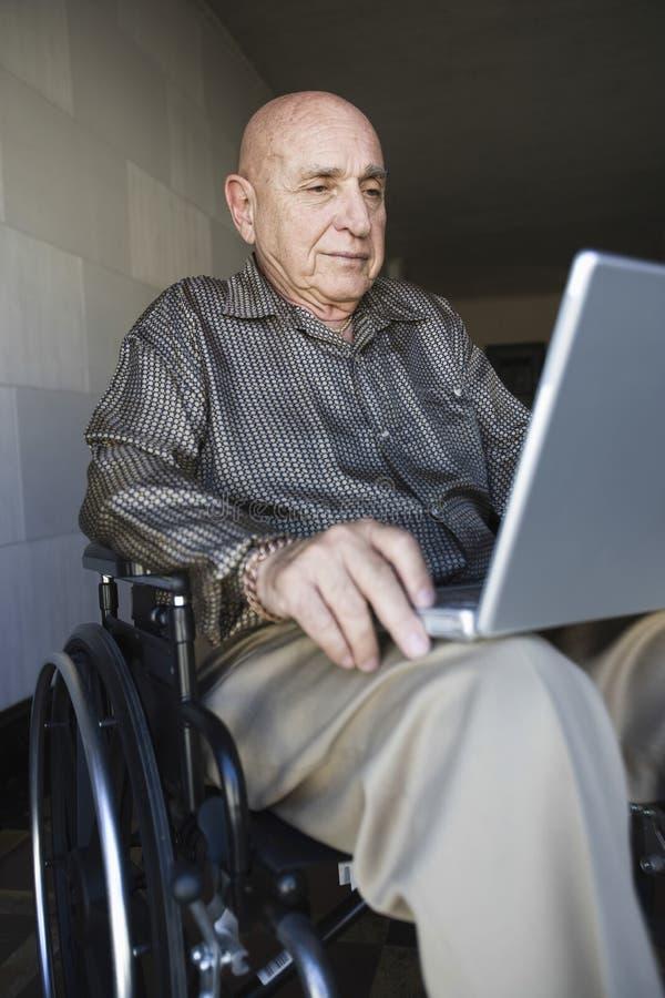 Mens in Rolstoel met Laptop stock foto's