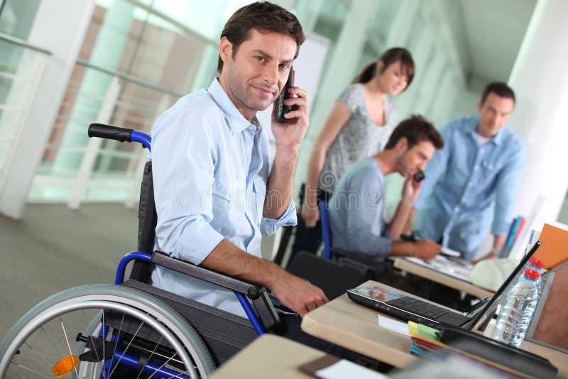 Mens in rolstoel met mobiel stock afbeelding