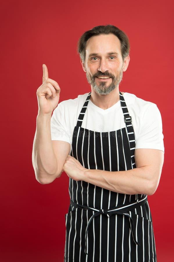 Mens in schort Zekere rijpe knappe mens op schort rode achtergrond Hij zou de chef-kok of de reinigingsmachine van de bakkerstuin stock afbeelding