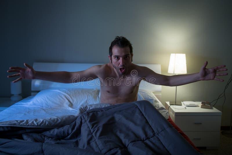 Mens slapeloos in zijn bed die na nachtmerrie gillen royalty-vrije stock afbeeldingen