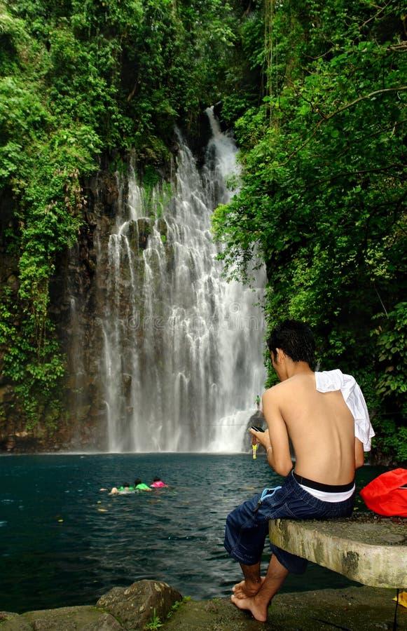 Mens SMS -sMS-ing dichtbij tropische waterval. royalty-vrije stock foto