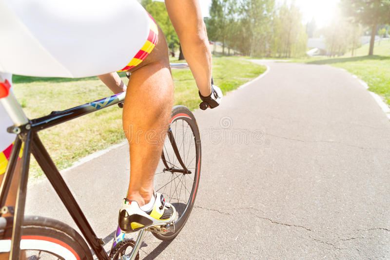 Mens sport riding a bicycle in the park at asphalt road. stock photo