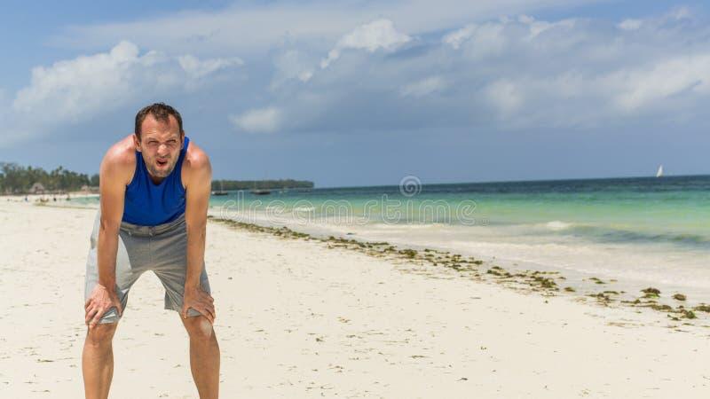 Mens in sportkleding die na oefening op strand rusten. royalty-vrije stock foto's