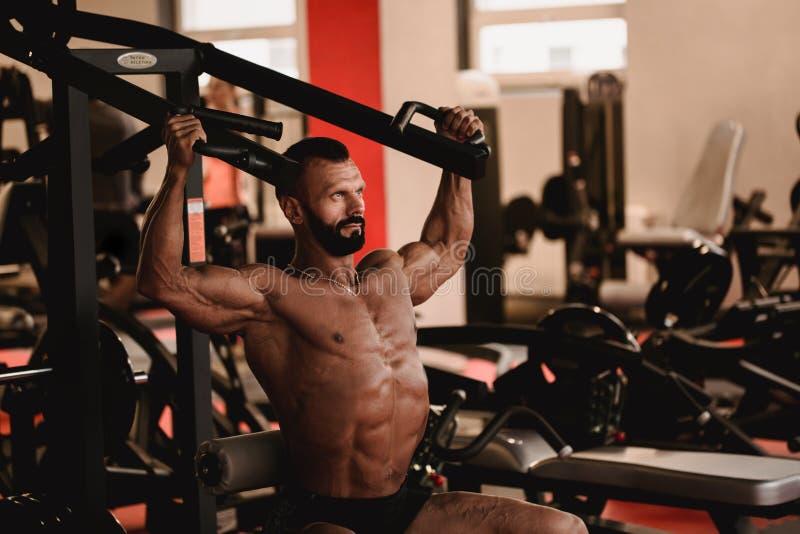 Mens in sportthema Sportman die in gymnastiek uitwerken Spierbodybuilder die oefeningen doen stock afbeeldingen