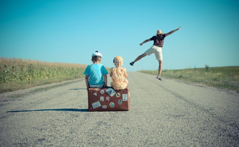 Mens springen en twee kinderen die op koffer zitten stock afbeeldingen